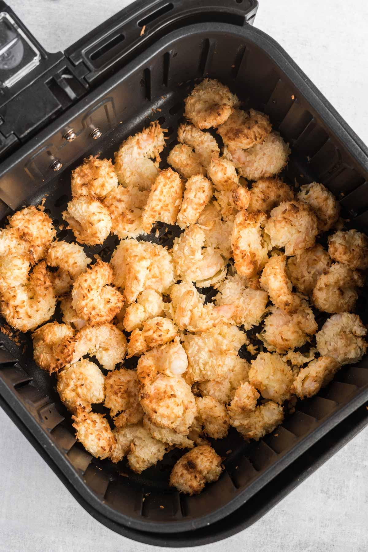 Air fried coconut shrimp in an air fryer basket.