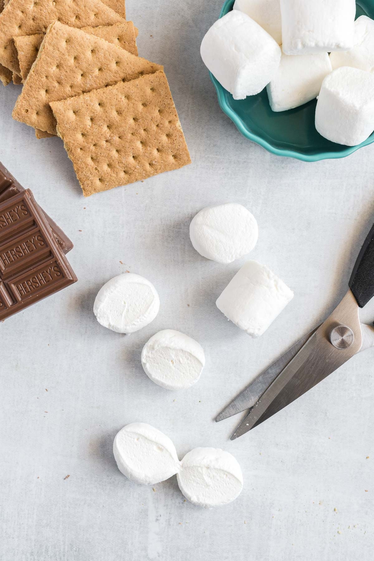 A stack of graham crackers and a bowl of marshmallows. Two marshmallows are cut in half and kitchen scissors are beside them.
