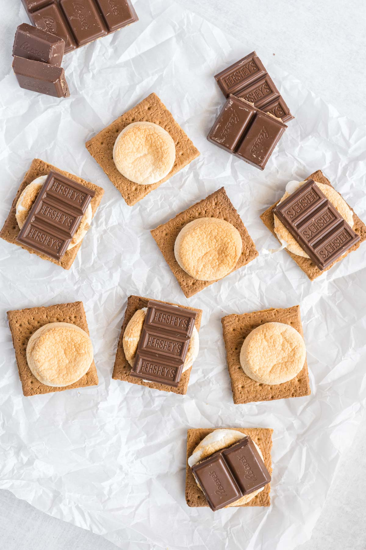 Graham cracker halves with toasted marshmallows and chocolate squares on half of them.