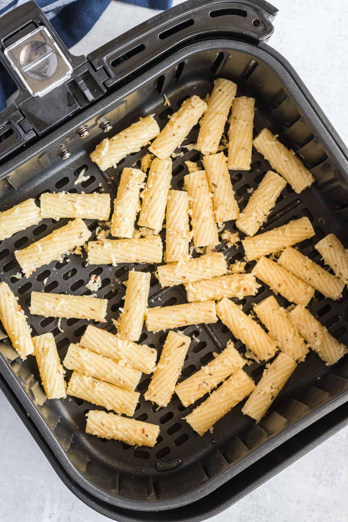Seasoned pasta in an air fryer basket.