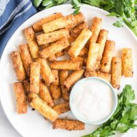 Crispy rigatoni on a plate with a small dish of garlic dip.