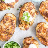 Twice baked potato halves with dishes of green onion and sour cream for topping.
