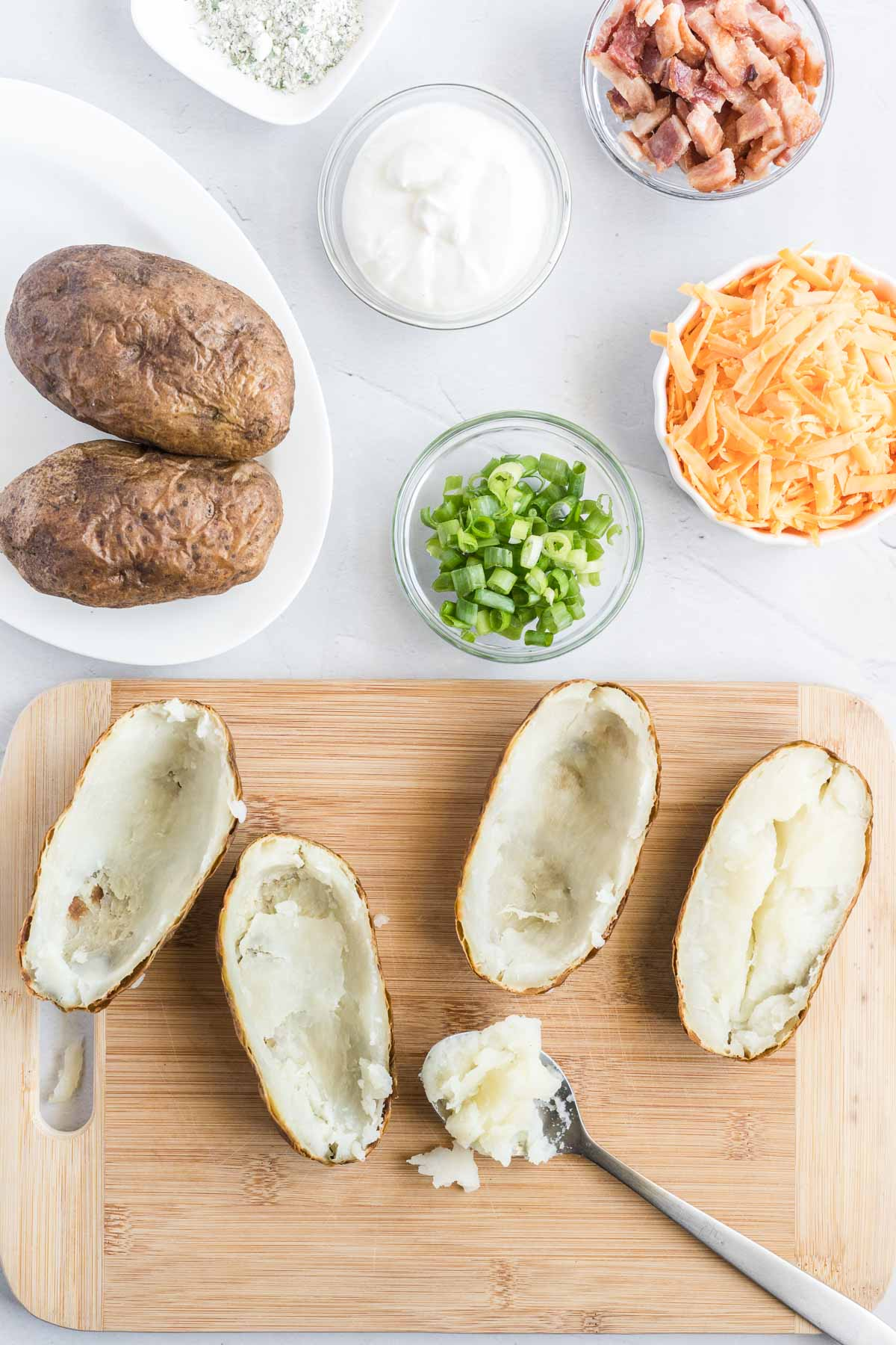 Baked potatoes cut in half with inside scooped out with a spoon.