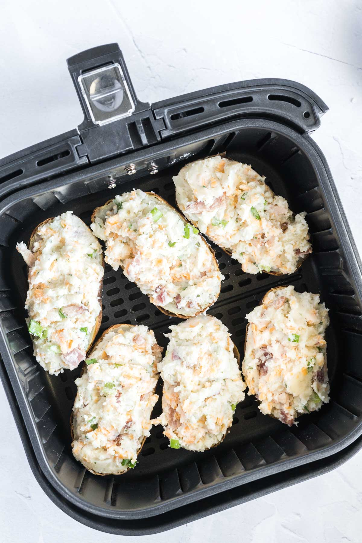 Six potato halves stuffed with filling in an air fryer basket.