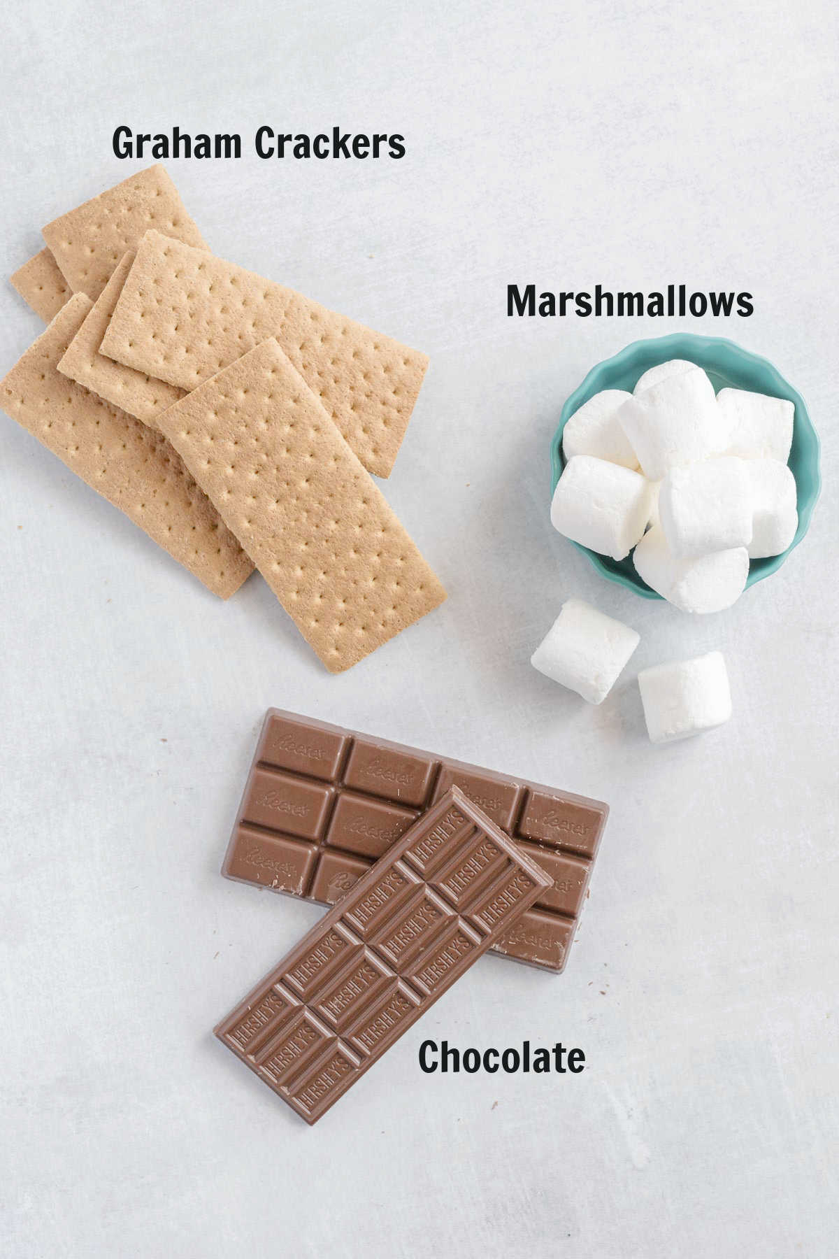 A stack of graham crackers, two chocolate bars and a bowl of large marshmallows.