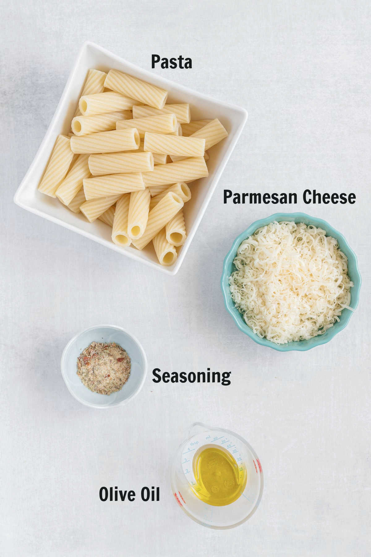 A bowl of cooked rigatoni, a dish of shredded parmesan, all purpose seasoning, and olive oil.