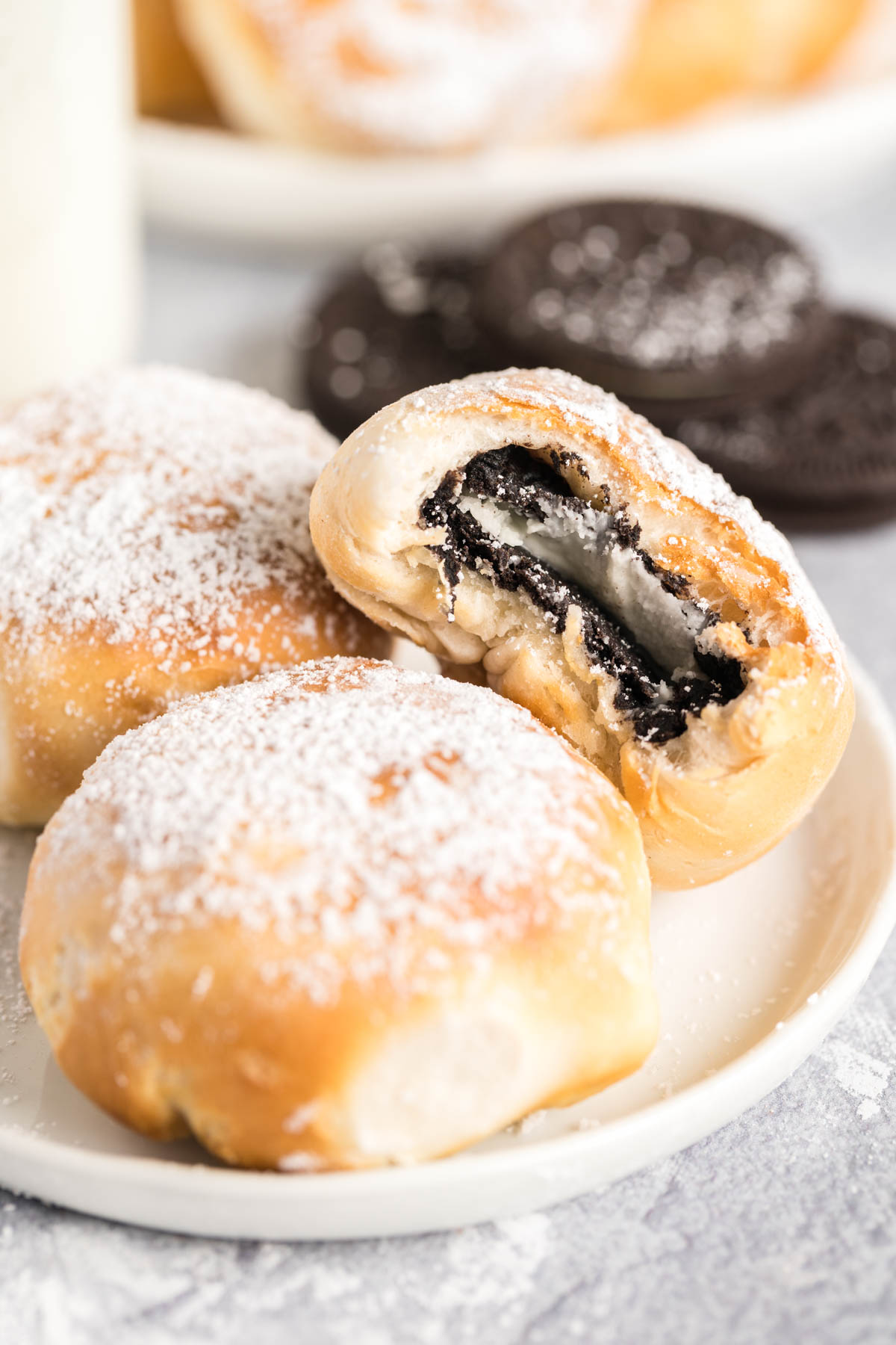 Oreo Cookies wrapped in dough and sprinkled with powdered sugar on a plate.