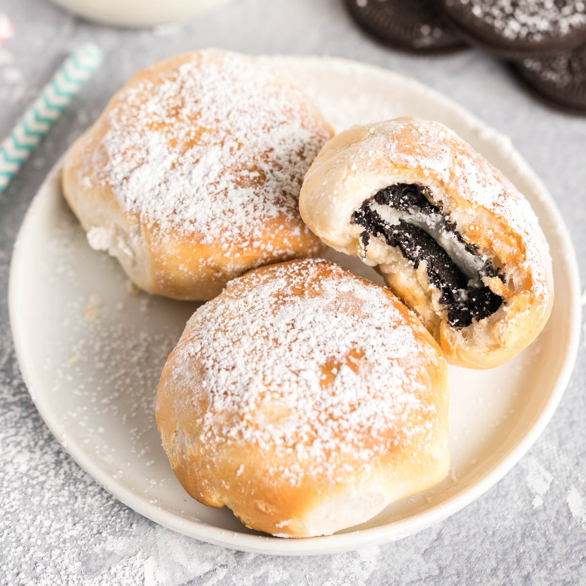 Three air fried Oreos dusted with powdered sugar on a plate.
