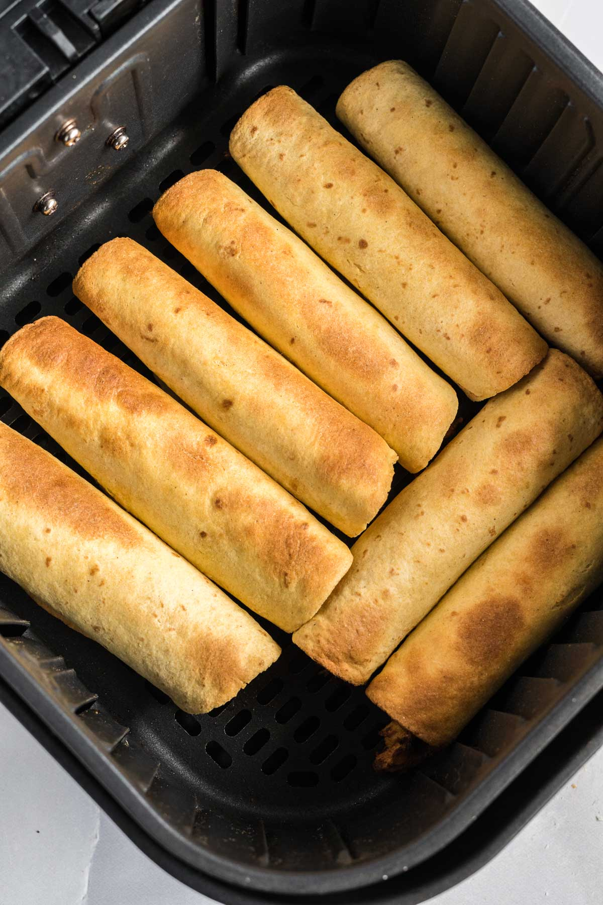 Cooked taquitos in a single layer in an air fryer basket.