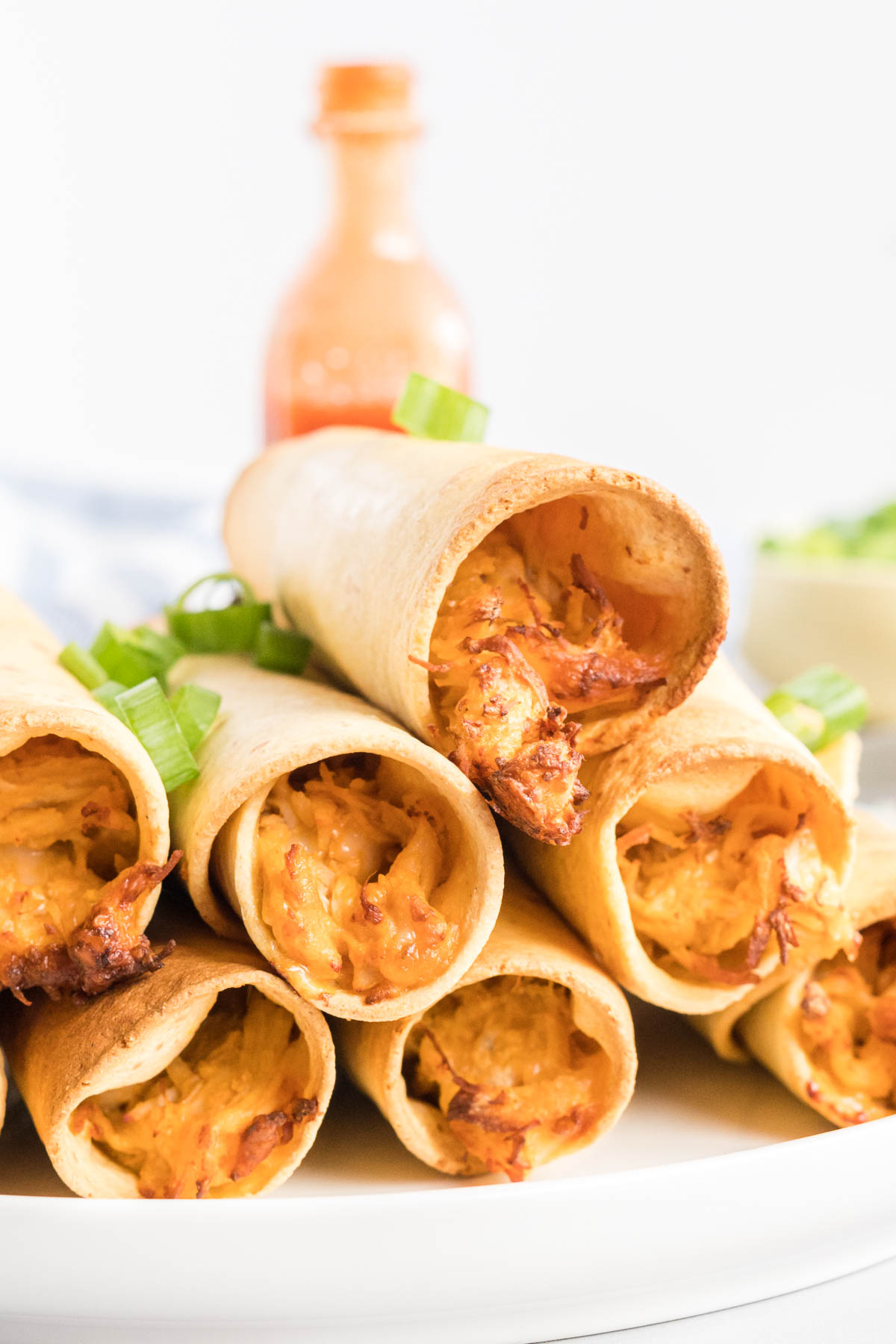 A stack of chicken taquitos on a plate.