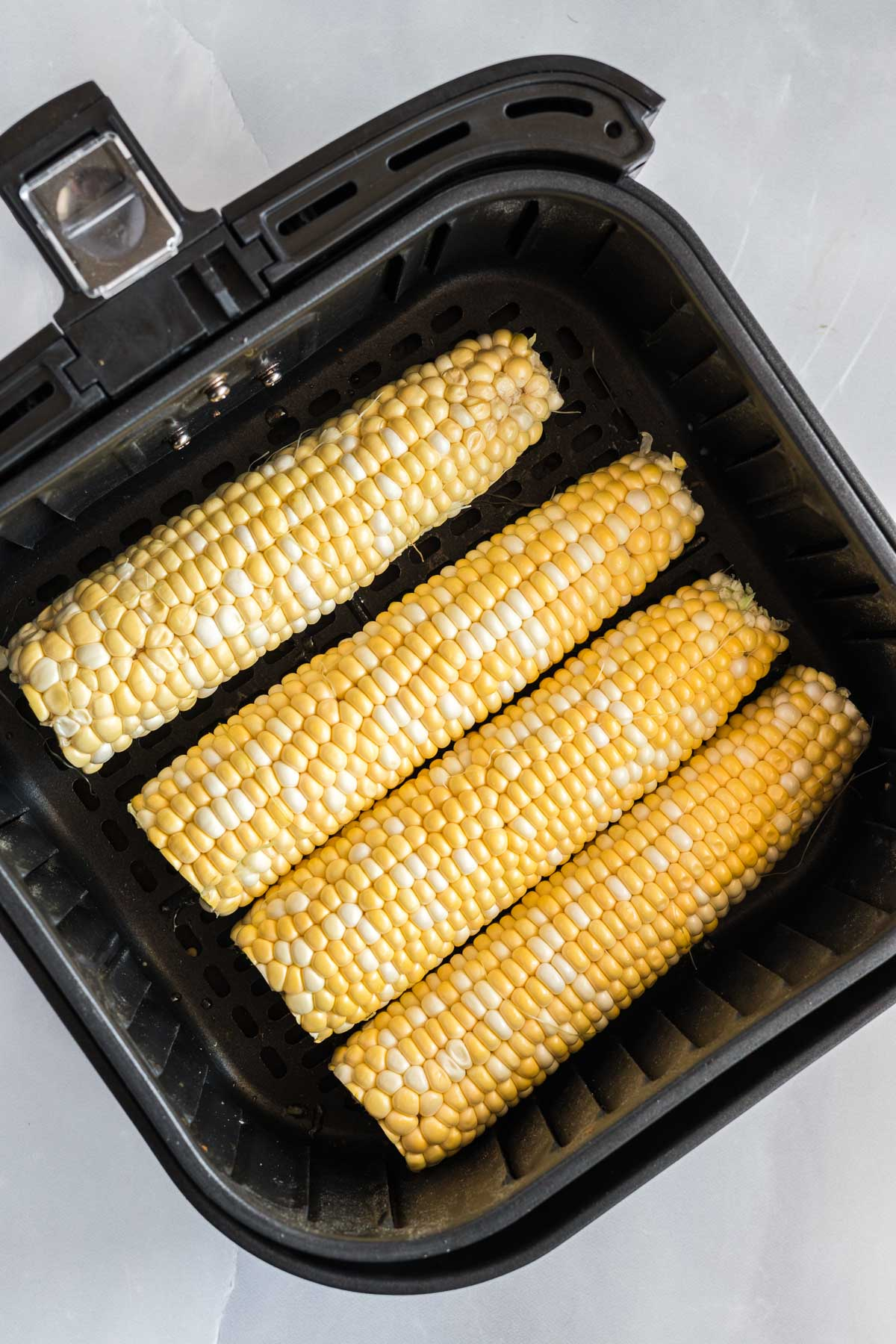 Raw corn on the cob in an air fryer basket.
