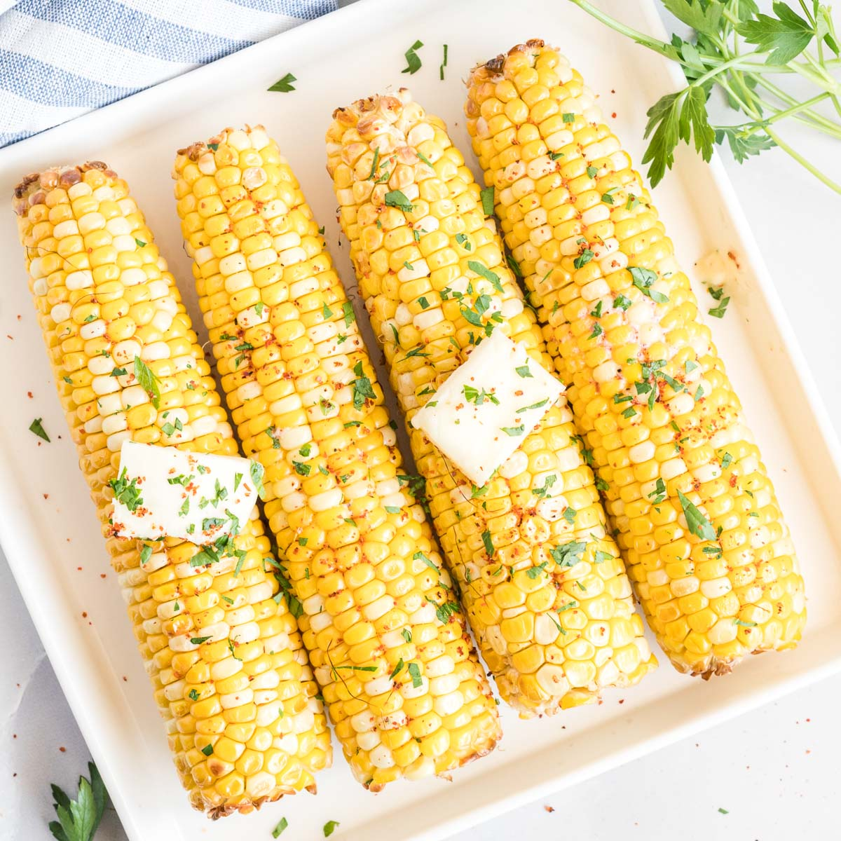 Corn on the cob on a plate topped with pats of butter, salt and chopped herbs.