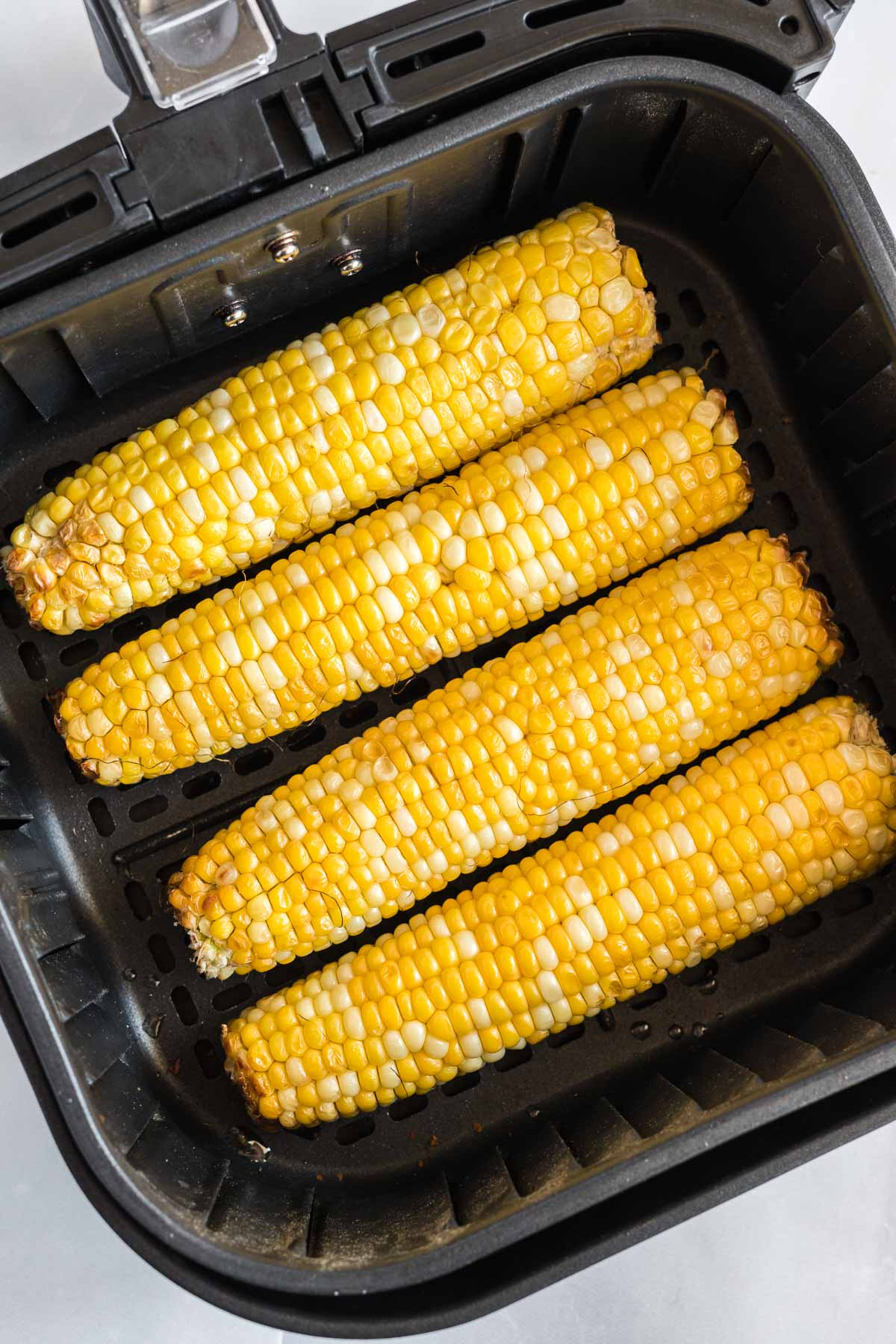 Four cooked corn on the cobs in an air fryer basket.