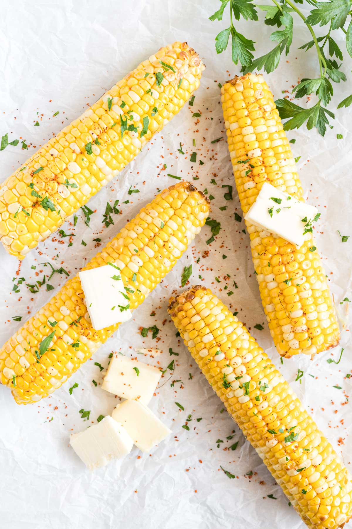 4 corn on the cobs with butter pats, salt and fresh chopped herbs.