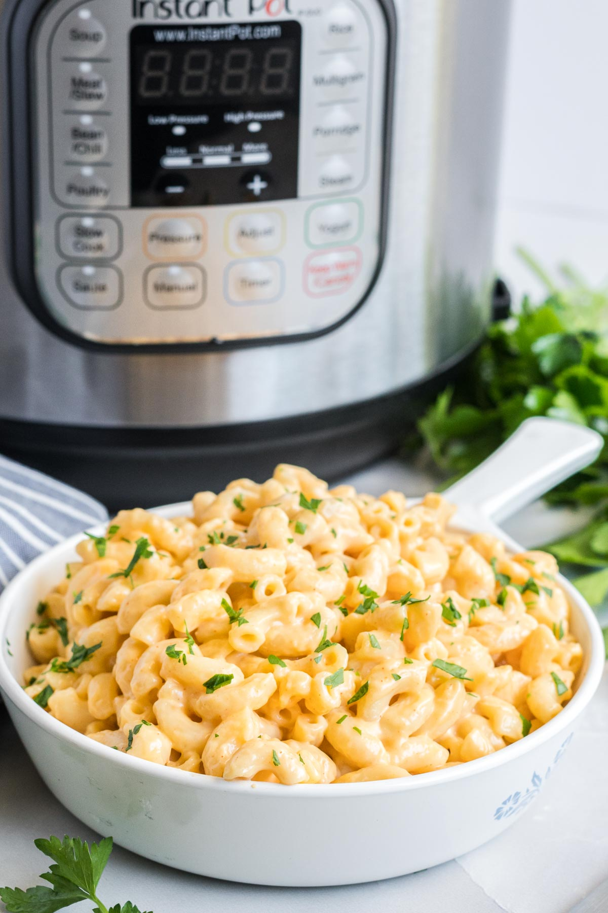 Mac and cheese in a serving dish with an instant pot in the background.